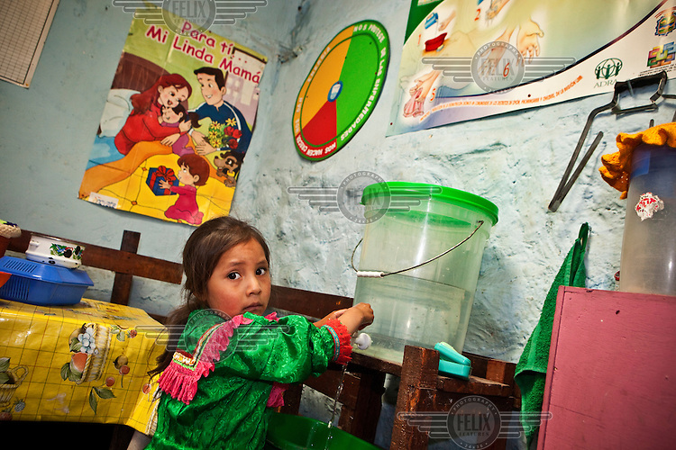 A girl washes her hands inside her home. This is part of a hand washing promotion campaign by the Peruvian NGO ADRA, which works with people affected by poverty and malnutrition in the region of Oyon. ADRA promotes healthy families through behavior change and management of housing.