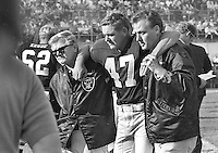 Raiders DB Kent McCloughan is helped off the field by Dick Romanski and trainer George Anderson. (1968 photo/Ron Riesterer)