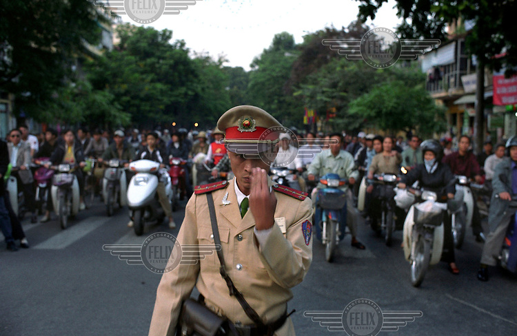 Policeman directing busy motorcycle traffic.