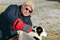 Wednesday March 14, 2007   ----   Dog lot volunteer John White of Vero Beach, Floriday lays on the snow to pet a Tolloff Monson dog at the dog lot in Nome