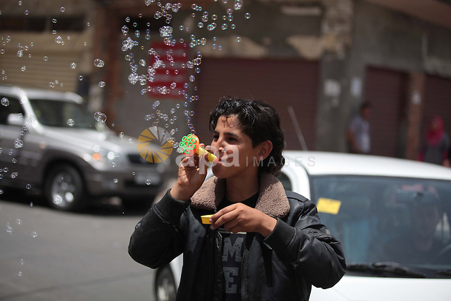 A Palestinian boy blows soap bubbles as he plays in Gaza City on June 03, 2014. Seventeen technocrat ministers were sworn in before Palestinian president Mahmoud Abbas as the incumbent Palestinian Prime Minister Rami Al Hamdallah will also head the new government as people of Gaza Strip hope that the new interim government brings them closer to an independent Palestinian state and lift the inhumane Israeli blockade. Photo by Ashraf Amra