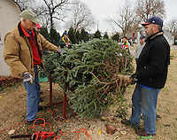 STAFF PHOTO ANDY SHUPE - Steve Langton, left, and Chris Harris, right, trim a tree for Eric and Elda Scott and their daughter, Ameila, 6, at the Rogers Optimist Club's annual Christmas tree lot Sunday, Dec. 7, 2014, in downtown Rogers. The lot is open seven days a week and raises money for local activities, funds and scholarships.