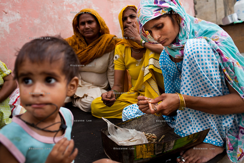 Nafeesa (right, in blue), 27, rolls bidis (indian cigarettes) with other village women as her children play in her house compound in a slum in Tonk, Rajasthan, India, on 19th June 2012. Nafeesa's health deteriorated from bad birth spacing and over-working. While her husband works far from home, she rolls bidis to make an income and support the family. She single-handedly runs the household and this has taken a toll on her health and financial insufficiencies has affected her children's health. Photo by Suzanne Lee for Save The Children UK