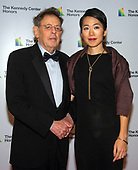 Philip Glass and his partner, Saori Tsukada, arrive for the formal Artist's Dinner honoring the recipients of the 41st Annual Kennedy Center Honors hosted by United States Deputy Secretary of State John J. Sullivan at the US Department of State in Washington, D.C. on Saturday, December 1, 2018. The 2018 honorees are: singer and actress Cher; composer and pianist Philip Glass; Country music entertainer Reba McEntire; and jazz saxophonist and composer Wayne Shorter. This year, the co-creators of Hamilton­ writer and actor Lin-Manuel Miranda, director Thomas Kail, choreographer Andy Blankenbuehler, and music director Alex Lacamoire will receive a unique Kennedy Center Honors as trailblazing creators of a transformative work that defies category.<br /> Credit: Ron Sachs / Pool via CNP
