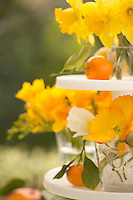 A colourful arrangement of garden flowers and small oranges on a three-tiered cake stand