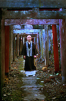 "Shinto priest, Kyosan, Japan 2005.<br /> A Shinto priest stands among the Tori gates of his shrine. Shinto, ""the way of the gods,"" is considered to be the indigenous spirituality of Japan's people and remains to be the most popular of the country's religion besides Buddhism."