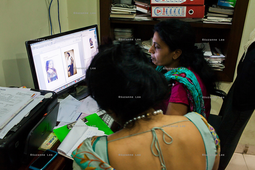 Dr. Nayana Patel, works with her assistant as they screen profiles of egg donors in her Akanksha IVF and surrogacy center in Anand, Gujarat, India on 10th December 2012. Surrogacy clients pour into Anand from across the world pursuing Dr Patel's expertise on the process, and they keep in touch with her and the progress of the pregnancies via the internet and phone. While 15% of couples are infertile globally, only 6% of infertility cases require surrogacy as a last option. Photo by Suzanne Lee / Marie-Claire France