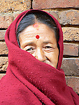A woman is wrapped in a red shawl against the winter chill