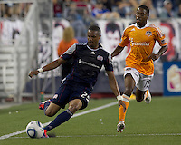 New England Revolution defender Darrius Barnes (25) passes the ball as Houston Dynamo midfielder Alex Dixon (19) closes. In a Major League Soccer (MLS) match, the New England Revolution tied Houston Dynamo, 1-1, at Gillette Stadium on August 17, 2011.