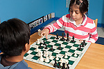 Afterschool chess program for elementary students graduates of Headstart program boy and girl playing together