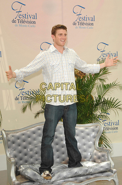 "BRYAN GREENBERG.attends a photocall promoting the television series ""October Road"" on the third day of the 2008 Monte Carlo Television Festival held at Grimaldi Forum in Monte Carlo, Principality of Monaco, June 10, 2008..full length standing on sofa couch hands shirt jeans plaid checked white.CAP/TTL .©TTL/Capital Pictures"