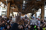 """Demonstrators stage a sit in with their hands up to chants of """"Don't shoot!"""" on Lake Street under the El in support a Citizens Police Accountability Council to provide civilian oversight of the Chicago Police Department in Chicago, Illinois on July 11, 2016.  The demonstration attracted a larger crowd on the heels of last week's racially charged police shootings captured on video of Alton Sterling in Baton Rouge, Louisiana and Philando Castile in the St. Paul suburb of Falcon Heights, Minnesota which was followed by a mass shooting of five police officers by Afghan War veteran Micah Johnson who supported radical and violent black nationalist ideology."""
