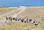 Refugees walk ashore from a beach near Molyvos, on the Greek island of Lesbos, on October 29, 2015, after they crossed the Aegean Sea from Turkey in a boat provided by Turkish traffickers to whom the refugees paid huge sums. They were received in Greece by local and international volunteers, then proceeded on their way toward western Europe.