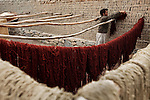 6 May 2009, Kabul, Afghanistan: Wool for a rug is hung to dry at  Arzu Rugs of Kabul, Afghanistan. Arzu  support women weavers in provincial Afghanistan providing incentives such as  cash bonuses for sold products as well as literacy programs. Workers dye wool in vats of boiling water with a variety of herbs and spices added to provide colour. The wool is then hung out on racks to dry at Arzu's headquarters before it is woven. Finally it id shaved then washed with soap and dried in the sun. Picture by Graham Crouch