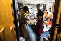 Die Sea Watch-2 Crew war am Freitag den 21. Oktober 2016 in den fruehen Morgenstunden waehrend ihrer 13. SAR-Mission vor der libyschen Kueste zu einer Position ausserhalb der 12 Meilenzone gerufen worden. Es war ein Fluechtlingsschlauchboot gesichtet worden. Als die Sea Watch-2 dort eintraf sah sie ca. 150 Menschen zusammengepfercht in einem ueberfuellten Schlauchboot sitzen. Eine Versorgung der Menschen auf dem Fluechtlingsschlauchboot mit Rettungswesten durch die Rettungs Boote der Sea Watch-2 wurde von der libyschen Kuestenwache unterbunden. Ein Soldat der Kuestenwache enterte das Schlauchboot vom Bug und machte sich dann an dem Aussenbordmotor zu schaffen. Auf dem Weg dahin schlug und trat er die Gefluechteten ein. Nach einigen Minuten entfernte sich das Boot der Kuestenwache. Dann verlor der Bug des Schlauchbootes seine Luft und es brach Panik bei den Gefluechteten aus. Sie sprangen in das Wasser und versuchten zum Schiff Sea Watch-2 zu gelangen. Die Crew warf ihnen Schwimmwesten und Rettungsringe zu, die Besatzungen der Rettungsboote der Sea Watch-2 zogen Menschen aus dem Meer, dennoch sind bis zu 30 Menschen ertrunken. Vier Ertrunkene konnten von der Sea Watch geborgen werden.<br /> Im Bild: Polizisten des norwegischen Frontex-Kommandos uebernehmen vier der am Morgen ertrunkenen Gefluechteten. Rechts ein Crewmitglied der Sea Watch-2.<br /> 21.10.2016, Mediterranean Sea<br /> Copyright: Christian-Ditsch.de<br /> [Inhaltsveraendernde Manipulation des Fotos nur nach ausdruecklicher Genehmigung des Fotografen. Vereinbarungen ueber Abtretung von Persoenlichkeitsrechten/Model Release der abgebildeten Person/Personen liegen nicht vor. NO MODEL RELEASE! Nur fuer Redaktionelle Zwecke. Don't publish without copyright Christian-Ditsch.de, Veroeffentlichung nur mit Fotografennennung, sowie gegen Honorar, MwSt. und Beleg. Konto: I N G - D i B a, IBAN DE58500105175400192269, BIC INGDDEFFXXX, Kontakt: post@christian-ditsch.de<br /> Bei der Bearbeitung der Dateiinformationen