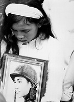 "Almost 400 men, women and children massacred by the Viet Cong during ""Tet 1968"" were mourned at a common-grave burial on October 14.  This young widow, carrying a photograph of her missing husband, mourns at the mass funeral service.  Hue, 1968.  (USIA)<br /> NARA FILE #:  306-MVP-4-8<br /> WAR & CONFLICT BOOK #:  427"