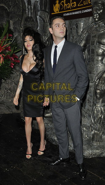 AMY WINEHOUSE & REG TRAVISS .Launch Party for 'Shaka Zulu' Private Members Club at Stables market, Camden,  London, England, UK,.August 4th 2010.full length black dress tattoos  grey gray suit tie white shirt couple boyfriend beige nude heels shoes hand in pocket peep toe cleavage low cut boobs boob job holding hands .CAP/CAN.©Can Nguyen/Capital Pictures.