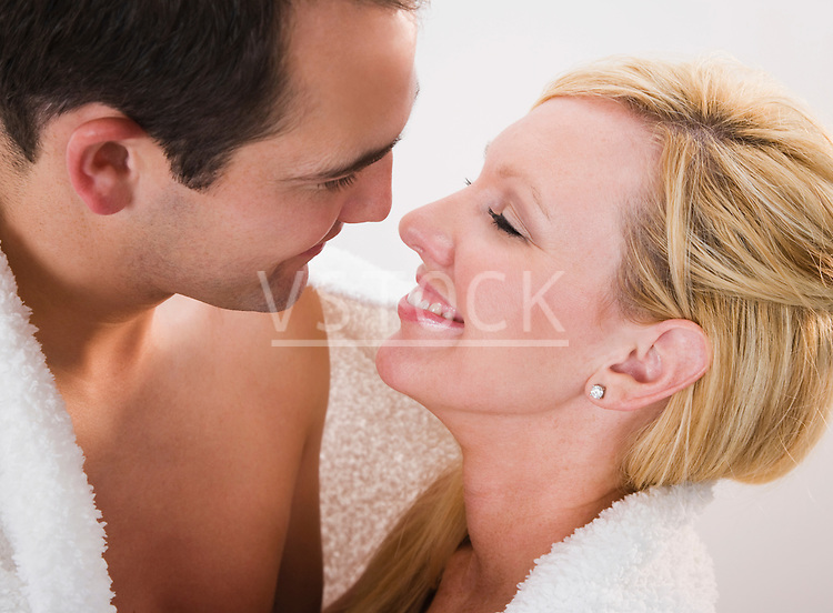 Couple wrapped in towel looking in eyes and smiling, close-up