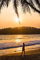 Mirissa Beach, tourist walking along the beach at sunset, South Coast of Sri Lanka, Southern Province, Asia. This is a photo of a tourist walking on Mirissa Beach at sunset, Sri Lanka, Asia. Mirissa Beach, a palm tree lined beach on the South Coast of Sri Lanka is one of the most popular tourist beaches and is host to many a beautiful sunset.