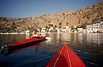 Crete, Greece, Sea kayakers ipaddle into coastal town of Souyia, southwest coast of Crete, Greece, Mediterranean Sea, Europe, Sarah Shannon, released, Circa 1990.