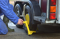 Attaching a security lock to a trailer wheel.