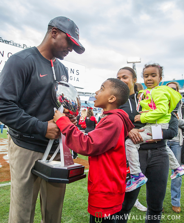 Georgia interim head coach Bryan McClendon and his 8 year-old son Bam looks at the TaxSlayer Bowl trophy after defeating Penn State 24-17 in an NCAA college football game in Jacksonville, Fla., Saturday, Jan. 2, 2016.  (AP Photo/Mark Wallheiser)