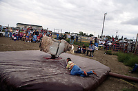 Competitors ride a mechanical bull at the Mechanical Bull-A-Rama at the Whoa Arena in Valier, Montana, USA.  The event, organized by Janelle Nelson, was a benefit for local youth rodeo participants and the local food bank.