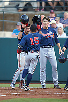 Willie Carter (15) of the Danville Braves is greeted at home plate by teammates Beau Philip (left) and Bryce Ball (19) after hitting a home run against the Pulaski Yankees at Calfee Park on June 30, 2019 in Pulaski, Virginia. The Braves defeated the Yankees 8-5 in 10 innings.  (Brian Westerholt/Four Seam Images)