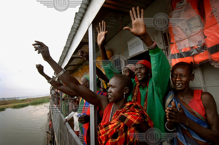 Women wave to people on the edge of the River Nile as they arrive in Bor on a barge returning Dinka tribespeople from Juba to their homeland after the civil war.  The resettlement programme is organised by the IOM (International Organisation for Migration).  Tens of thousands of Dinka tribespeople are among the estimated 3.8 million people displaced during the two-decade long conflict between the government and the SPLA (Sudanese People Liberation Army)...