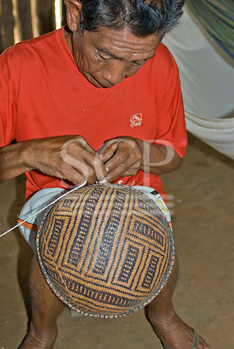 Xingu Indigenous Park, Mato Grosso State, Brazil. Aldeia Tuiarare (Kaiabi). Mo'yt Kaiabi. Teacher of handicraft with a traditional basket he has made.
