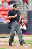 Home plate umpire Jose Esteras hustles down the first base line during a South Atlantic League game between the Kannapolis Intimidators and the Hickory Crawdads at  L.P. Frans Stadium August 1, 2010, in Hickory, North Carolina.  Photo by Brian Westerholt / Four Seam Images