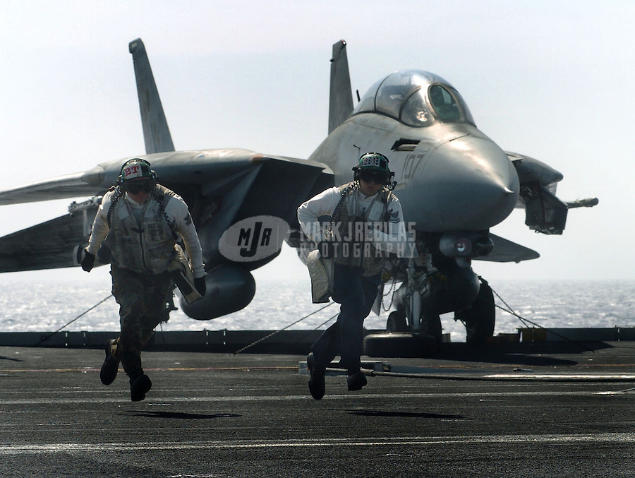 """Pacific Ocean (Mar. 25, 2004) -Sailors run across the flight deck aboard USS John C. Stennis (CVN 74) after performing maintenance on an F-14D Tomcat of the """"Tomcatters"""" of Fighter Squadron Three One (VF-31). Stennis and her embarked Carrier Air Wing Fourteen (CVW-14) are currently at sea conducting training exercises. Photo by Mark J. Rebilas"""