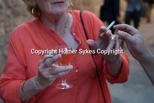 Smoking two cigarettes at once, and holding a glass of wine, drinking. France 2016
