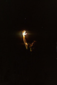 Xingu, Brazil. Sting holding his hand up to the light in an Indian oca house; Xingu Indigenous area, Nov 1990.