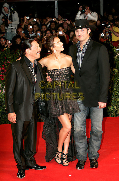 "DANNY TREJO, JESSICA ALBA & ROBERT RODRIGUEZ.""Machete"" premiere during the 67th Venice International Film Festival, Venice, Italy..September 1, 2010.full length black strapless dress mini train strappy sandals shoes circles sheer  lace suit jeans denim hat jacket profile tall short.CAP/PE.©Peter Eden/Capital Pictures."