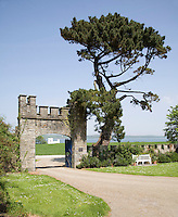 The miniature fort on the banks of the Shannon is framed in the gothic gateway at the entrance to Glin Castle