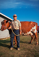 A dairy farmer and his prize milking cow. New Hampshire.