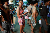 Peef Bancha, a 21 year old transgender waits with young men to speak to officers during the army draft held at a school in Klong Toey, the dockside slum area in Bangkok April 7, 2013. Men over 21 must serve in the army, which has always been at the forefront of Thai politics but has come in for some rare criticism since 91 people died in anti-government protests in 2010. Those who volunteer serve six months, but others choose the annual lottery, which goes on for 10 days in recruitment centres around Thailand. Nobody wants a red card, which means serving for two years, with the chance of a posting in the dangerous south. Only those not considered physically capable of service, the mentally ill and those who have significantly altered their physical appearance - such as transgenders, who are more visible in Thai society than in many other nations - are exempt.   REUTERS/Damir Sagolj (THAILAND)