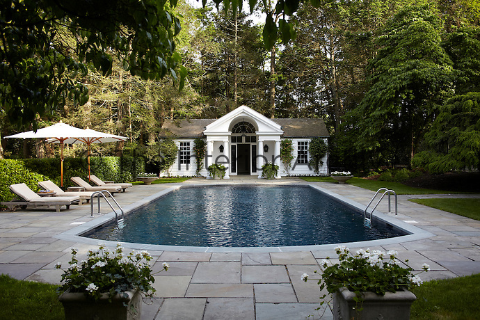 The outdoor swimming pool is graced with a classical poolhouse