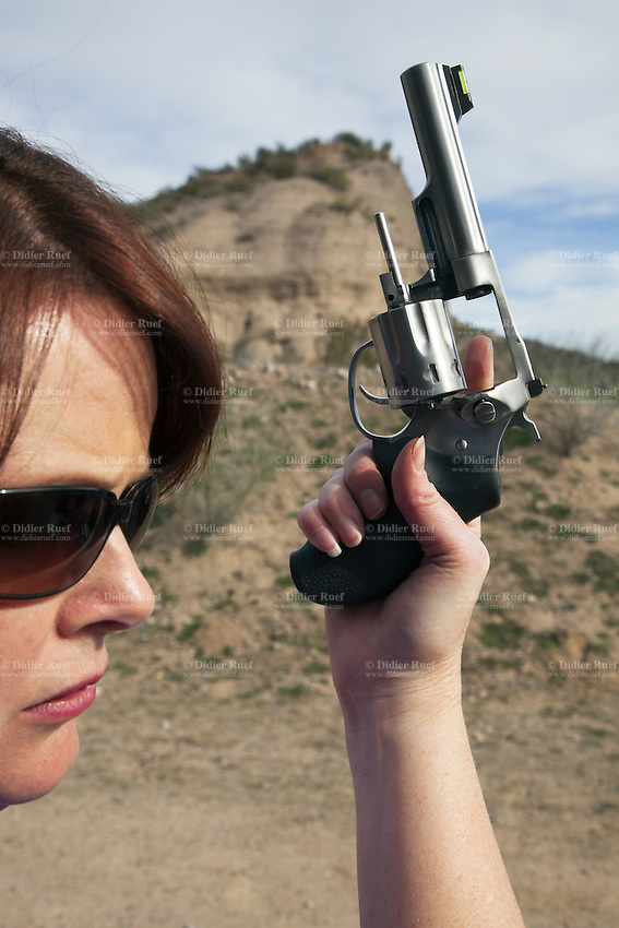 USA. Arizona state. Kearny town. Copper Basin Sportsmen's Club. Marti Stonecipher shows that the barrrel of her BlackHawk Ruger single 6 .22 cal pistol is empty. She is a certified instructor NRA Basic Pistol, NRA PPITH, NRA Range Safety Officer. Copper Basin Sportsmen's Club is a membership Range complex which purpose is to promote the sport of shooting and providing a safe, fun, family oriented environment. A firearm is a portable gun, being a barreled weapon that launches one or more projectiles often driven by the action of an explosive force. Most modern firearms have rifled barrels to impart spin to the projectile for improved flight stability. The word firearms usually is used in a sense restricted to small arms (weapons that can be carried by a single person). The right to keep and bear arms is a fundamental right protected in the United States by the Second Amendment of the Bill of Rights in the Constitution of the United States of America and in the state constitutions of Arizona and 43 other states. 29.01.16 © 2016 Didier Ruef