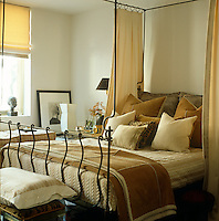 In a bedroom of a New York town house an air of intimacy and comfort has been created by piling the wrought iron bed with a collection of cushions in varying textures, patterns and tones