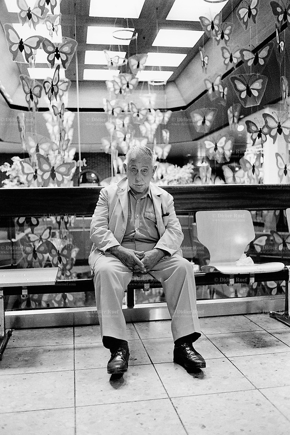 Switzerland. Canton Zürich. Winterthur. An old man half asleep sits alone on a chair in a shopping center. Plastic fake butterflies are hanged from the ceiling and used as decorations. © 1990 Didier Ruef