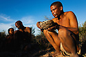 Botswana, Kalahari, bushman (san) holding tortoise shell containing gathered food