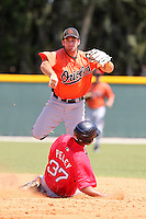 Baltimore Orioles minor league player Bobby Stevens #45 attempts to turn a double play as Josue Peley #37 slides in during a spring training game vs the Boston Red Sox at the Buck O'Neil Complex in Sarasota, Florida;  March 22, 2011.  Photo By Mike Janes/Four Seam Images