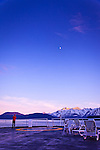 A man taking a photo from Alaska Marine Highway ferry's deck.  Alpenglow on Chilkat Mountains, crescent moon above the peaks, Inside Passage near Haines, SE Alaska in early summer.
