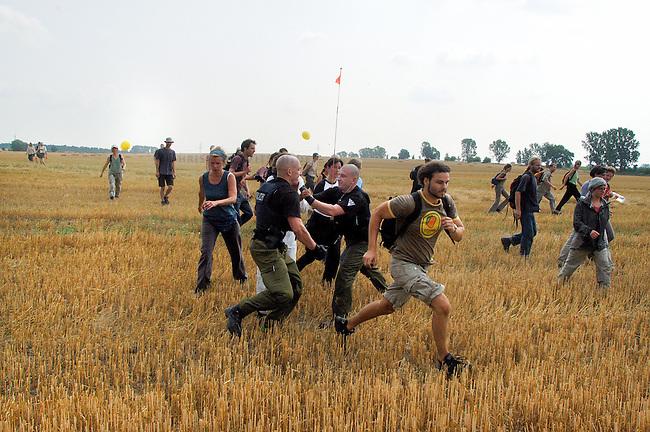 Aktion gegen Genmais in Brandenburg<br /> Trotz eines Grossaufgebotes an Polzei aus Berlin und Brandenburg gelang es kanpp 80 Menschen auf ein Genmaisfeld bei Zehdenick-Badingen in Brandenburg zu gelangen und dort mehrere hundert Quadratmeter Maispflanzen zu zerstoeren. Ca. 250 Menschen hatten sich im Vorfeld der angekuendigten Aktion shcriftlich bereit erklaert auf  das Feld zu gehen um den gentechnisch manipulierten Mais des US-Saatgutmultis Monsanto in einer gewaltfreien Aktion zu &quot;befreien&quot;. <br /> Mehrere dutzend Menschen wurden von der Polizei festgenommen.<br /> Hier: Einer speziellen Festnahmeeinheit der Polizei gelingt es nicht die Menschen am betreten des Feldes zu hindern.<br /> 30.7.2006, Zehdenick-Badingen/Brandenburg<br /> Copyright: Christian-Ditsch.de<br /> [Inhaltsveraendernde Manipulation des Fotos nur nach ausdruecklicher Genehmigung des Fotografen. Vereinbarungen ueber Abtretung von Persoenlichkeitsrechten/Model Release der abgebildeten Person/Personen liegen nicht vor. NO MODEL RELEASE! Nur fuer Redaktionelle Zwecke. Don't publish without copyright Christian-Ditsch.de, Veroeffentlichung nur mit Fotografennennung, sowie gegen Honorar, MwSt. und Beleg. Konto: I N G - D i B a, IBAN DE58500105175400192269, BIC INGDDEFFXXX, Kontakt: post@christian-ditsch.de<br /> Bei der Bearbeitung der Dateiinformationen darf die Urheberkennzeichnung in den EXIF- und  IPTC-Daten nicht entfernt werden, diese sind in digitalen Medien nach &sect;95c UrhG rechtlich geschuetzt. Der Urhebervermerk wird gemaess &sect;13 UrhG verlangt.]