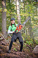 A female mountain biker poses with a chainsaw while clearing trail in Copper Harbor, Michigan.