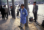 Beijing China 1990s. Unemployed people wait for job opportunities. The hand written sign on his jacket advertising his skills. 1995