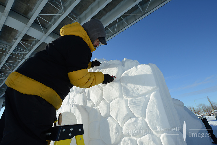 Jesse Mellor takes advantage of the bright winter sun to begin work on his snow sculpture, one of the premier events of the Anchorage, Alaska, Fur Rendezvous winter carnival in February, 2013.