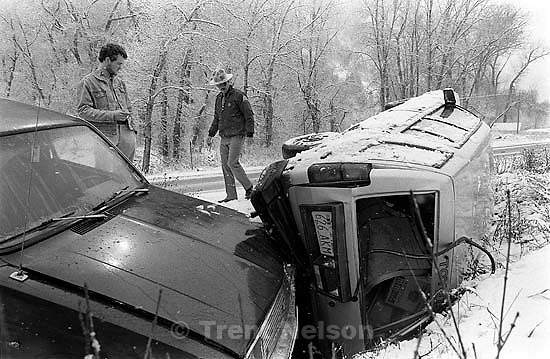 Car crash in snowy Provo Canyon. The driver of car at left (in jean jacket) smashed into the car on right while I was there shooting the first car. After impact, he looked up at me with a beer bottle in his hands.<br />
